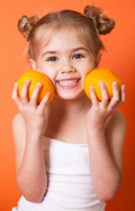 girl smiling holding oranges
